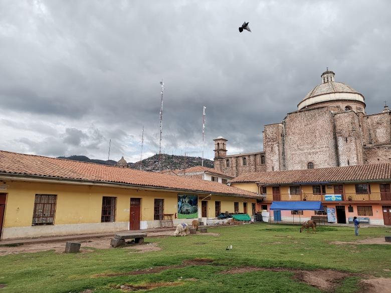 Patio with yellow colonial building and llamas in Cusco old-town