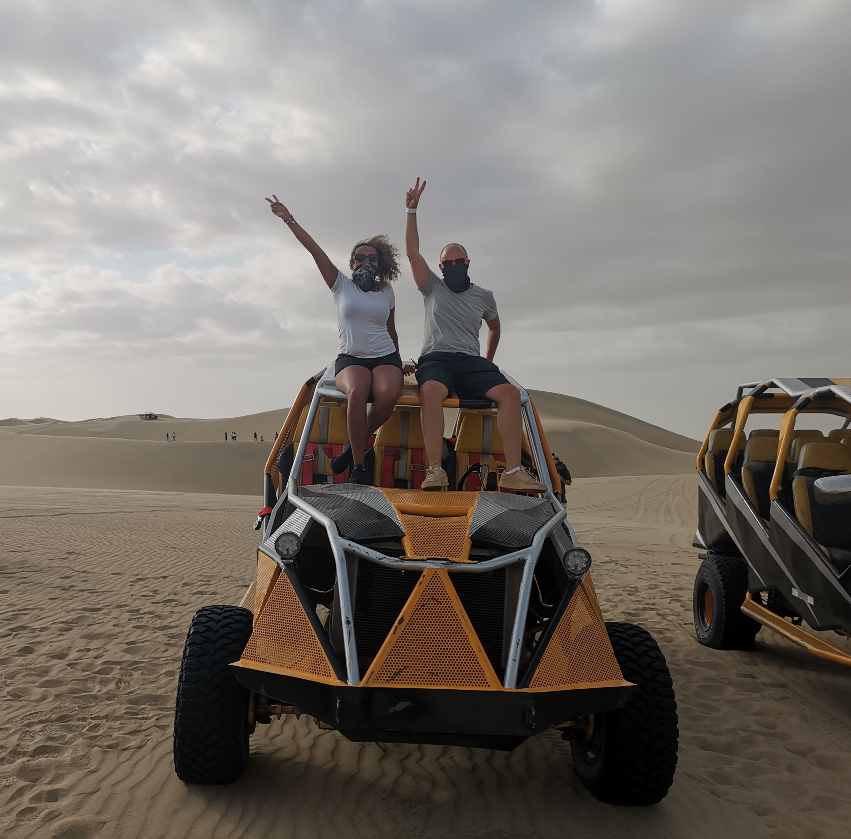 Couple at the top of buggy car in Huacachina oasis
