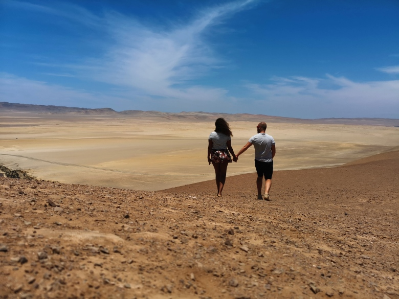Couple holding hands in Paracas Desert at the National Reserve